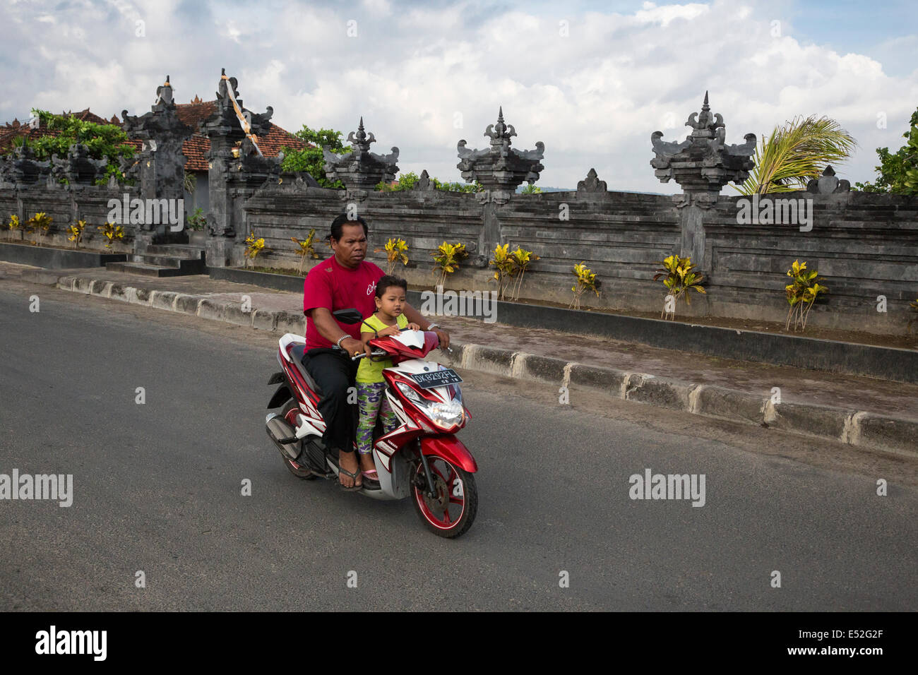 Bali, Indonesia.  Road safety.  Father and Daughter on Motorbike, no helmets. - Stock Image