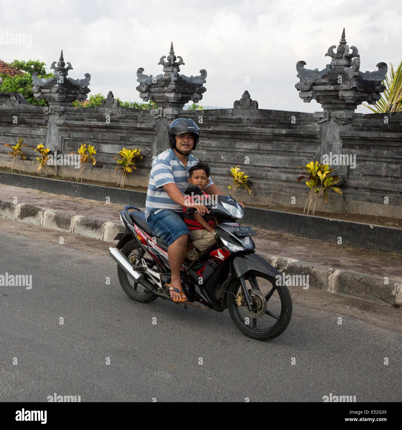 Bali, Indonesia.  Road safety.  Father and Son on Motorbike, no helmet on Boy. - Stock Image