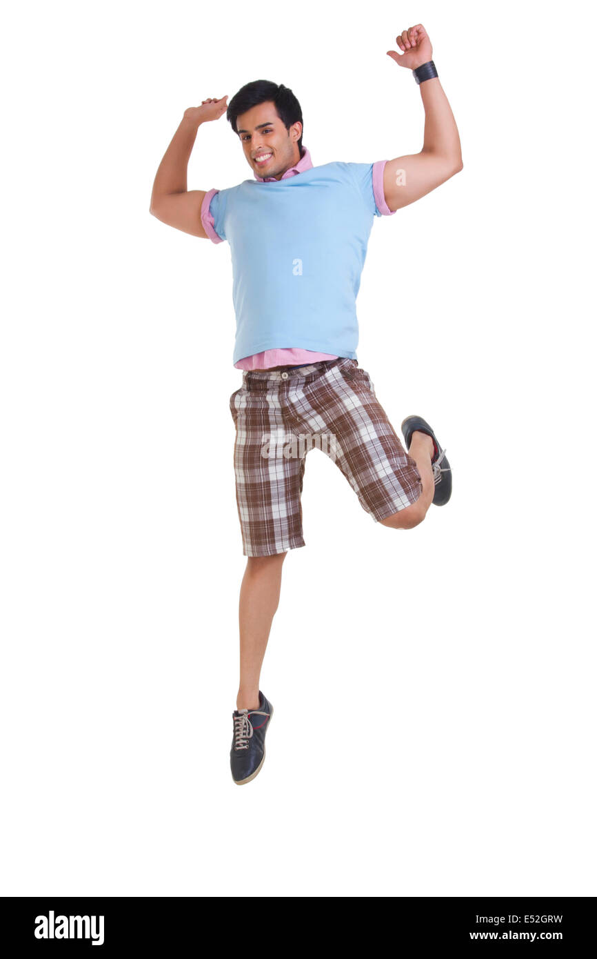Full length of young man in casuals jumping isolated over white background - Stock Image