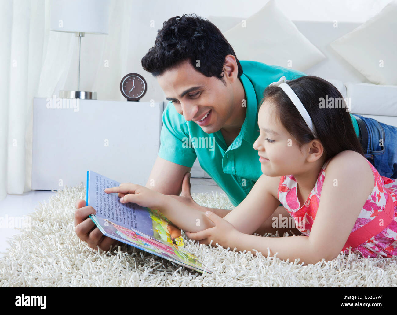 Father and daughter reading story book while lying on rug at home - Stock Image