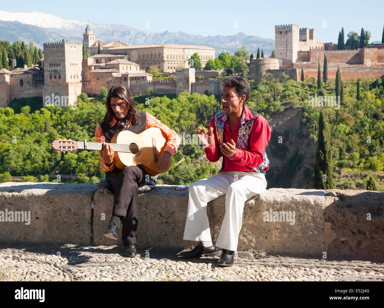 Flamenco musicians play with a backdrop of snow capped Sierra Nevada mountains and the Alhambra, Granada, Spain - Stock Image