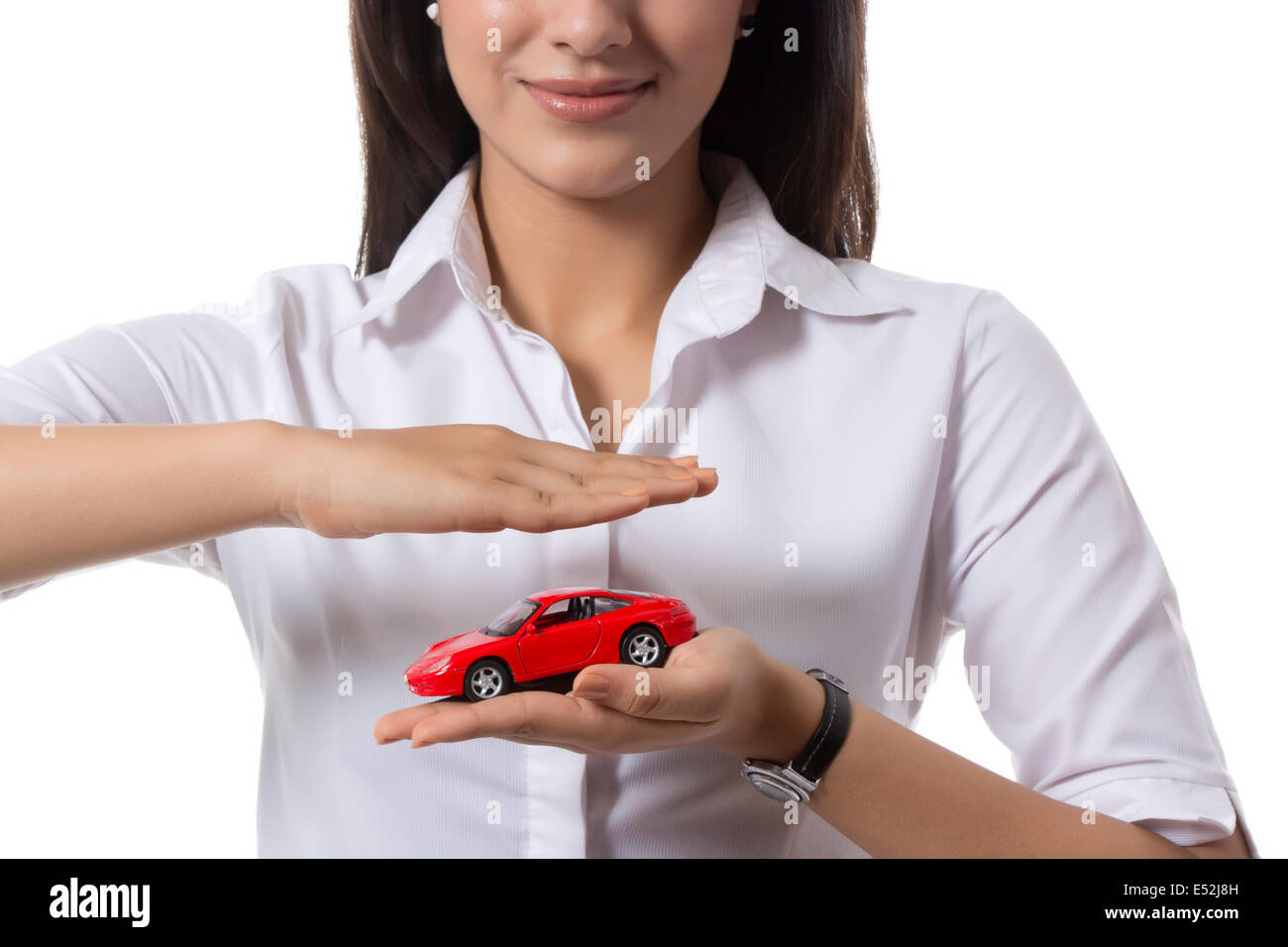 Midsection of young female insurance agent holding toy car against white background - Stock Image