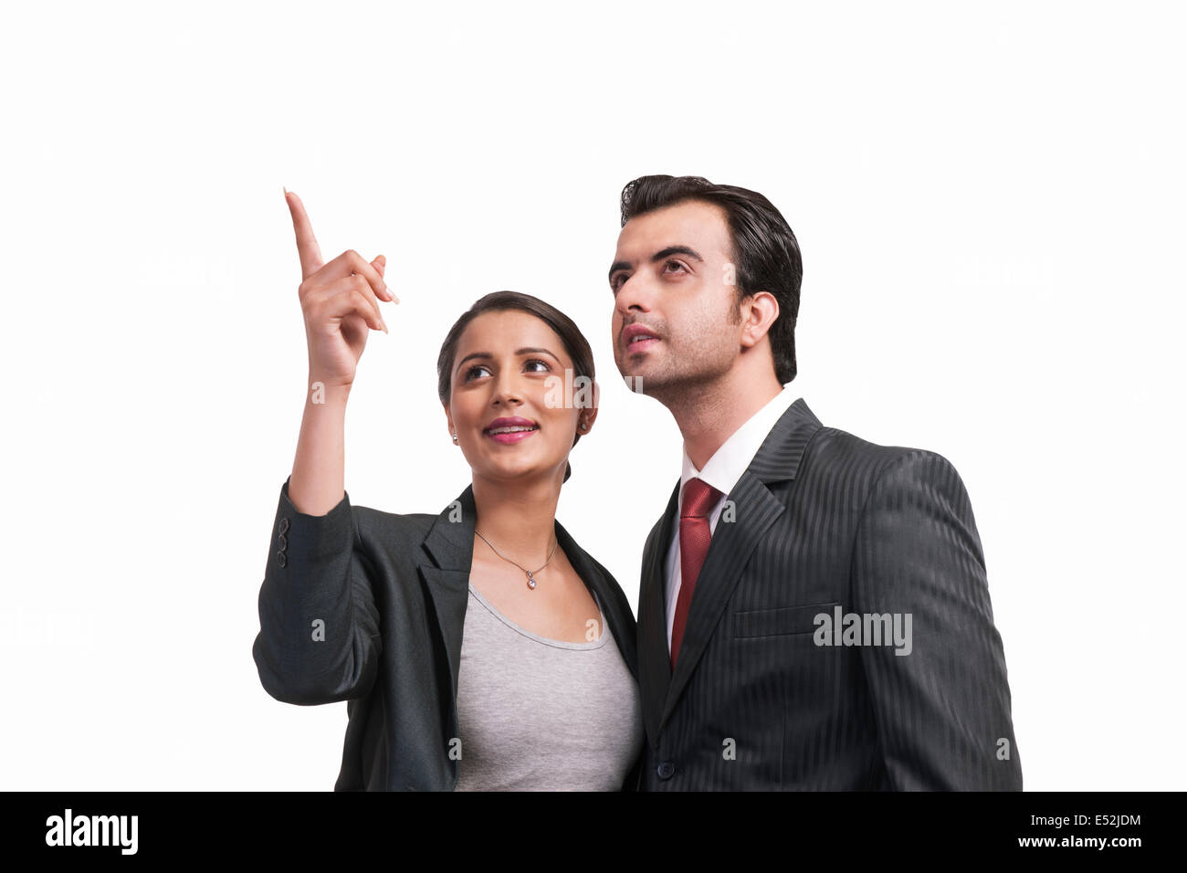 Beautiful businesswoman showing something to colleague over white background - Stock Image