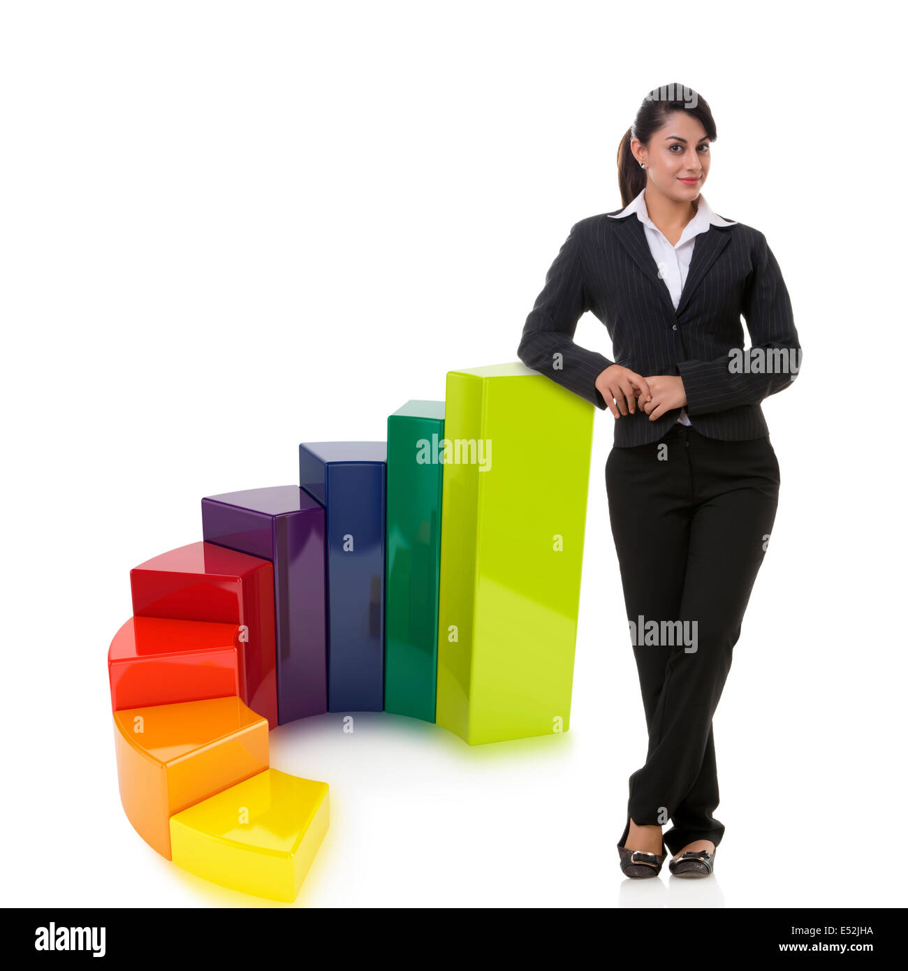 Portrait of confident businesswoman with multi colored bar graph representing growth over white background - Stock Image