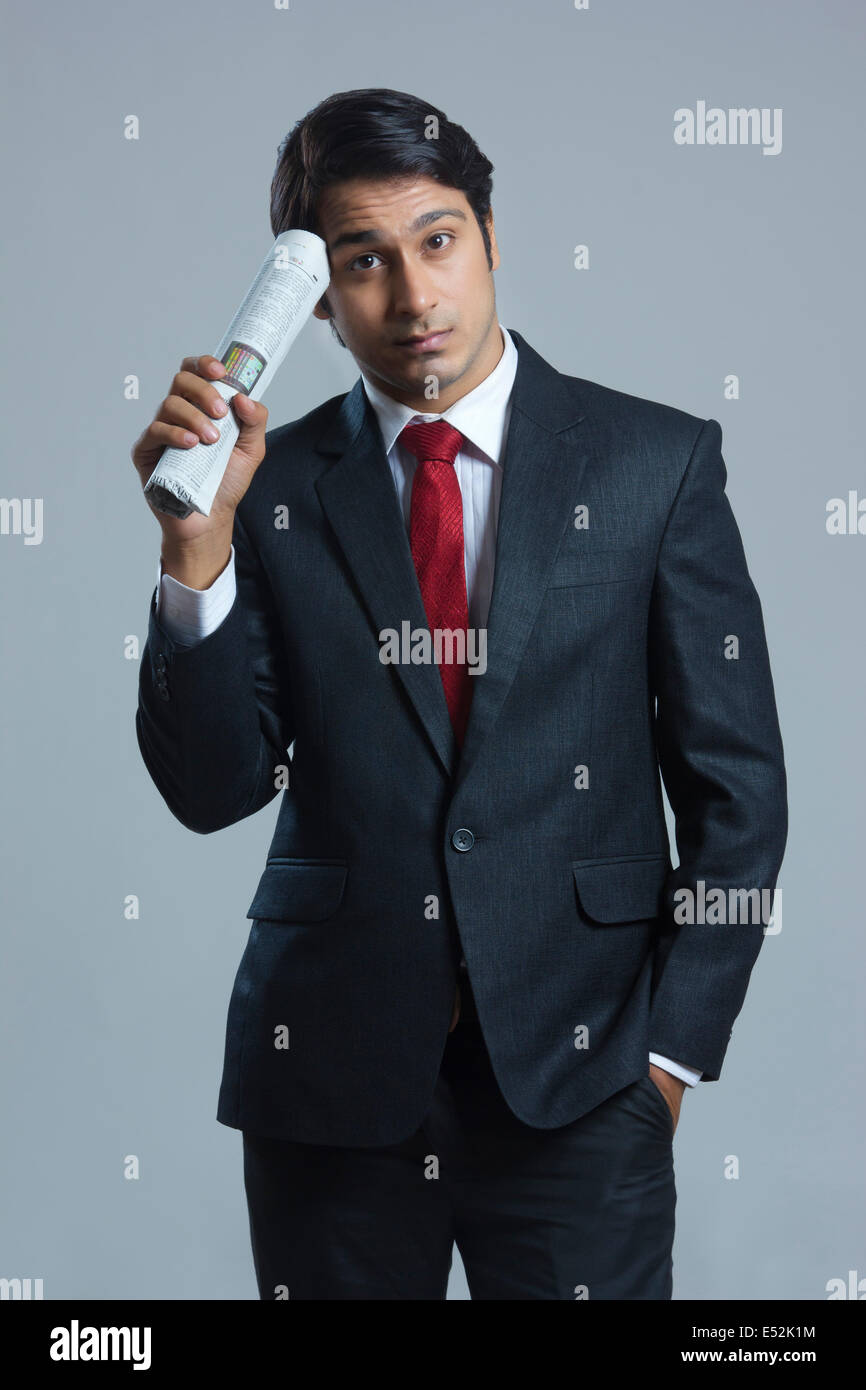 Portrait of confused businessman holding newspaper over gray background Stock Photo