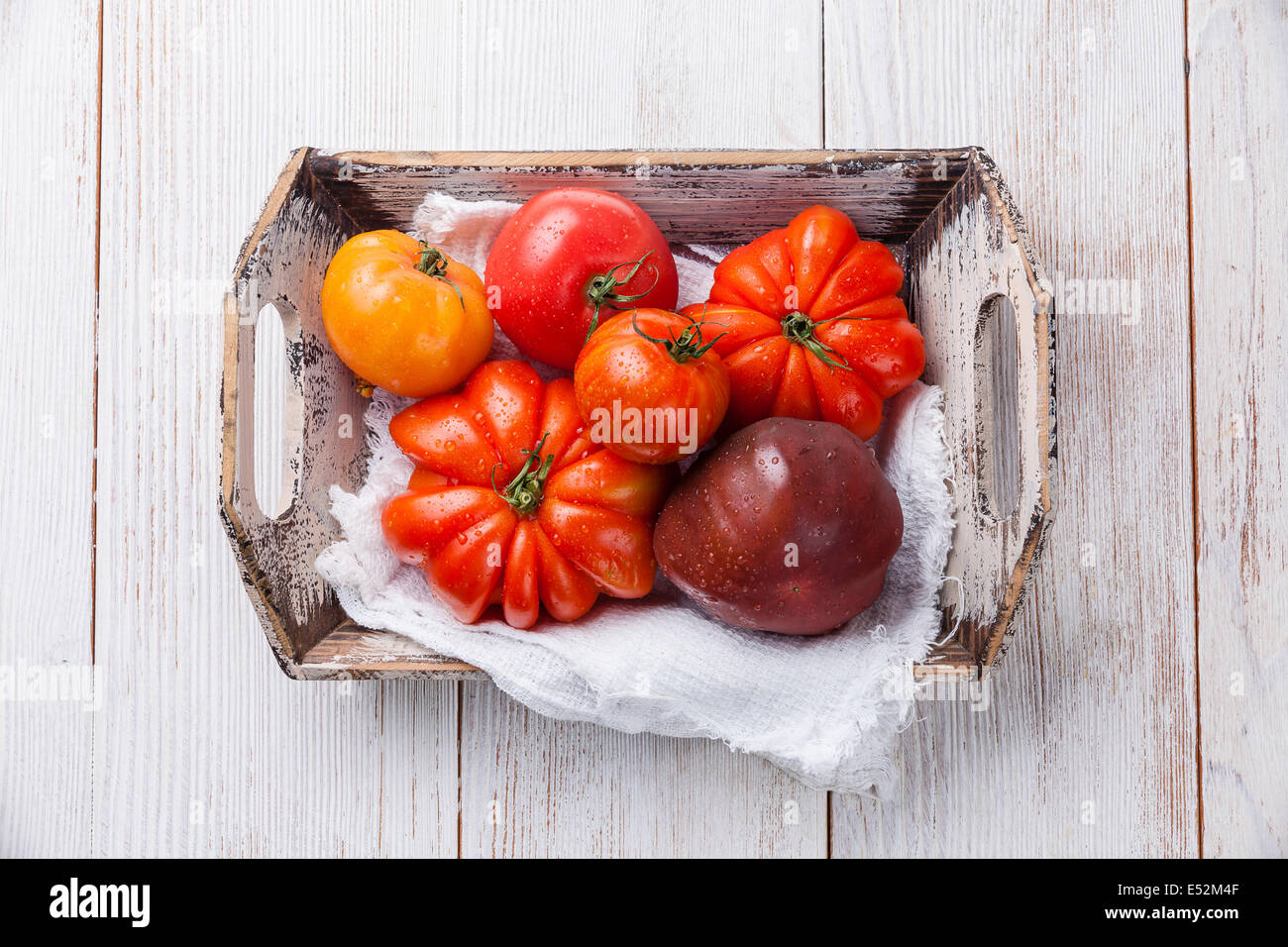 Ripe fresh colorful tomatoes in wooden box on white wooden background - Stock Image