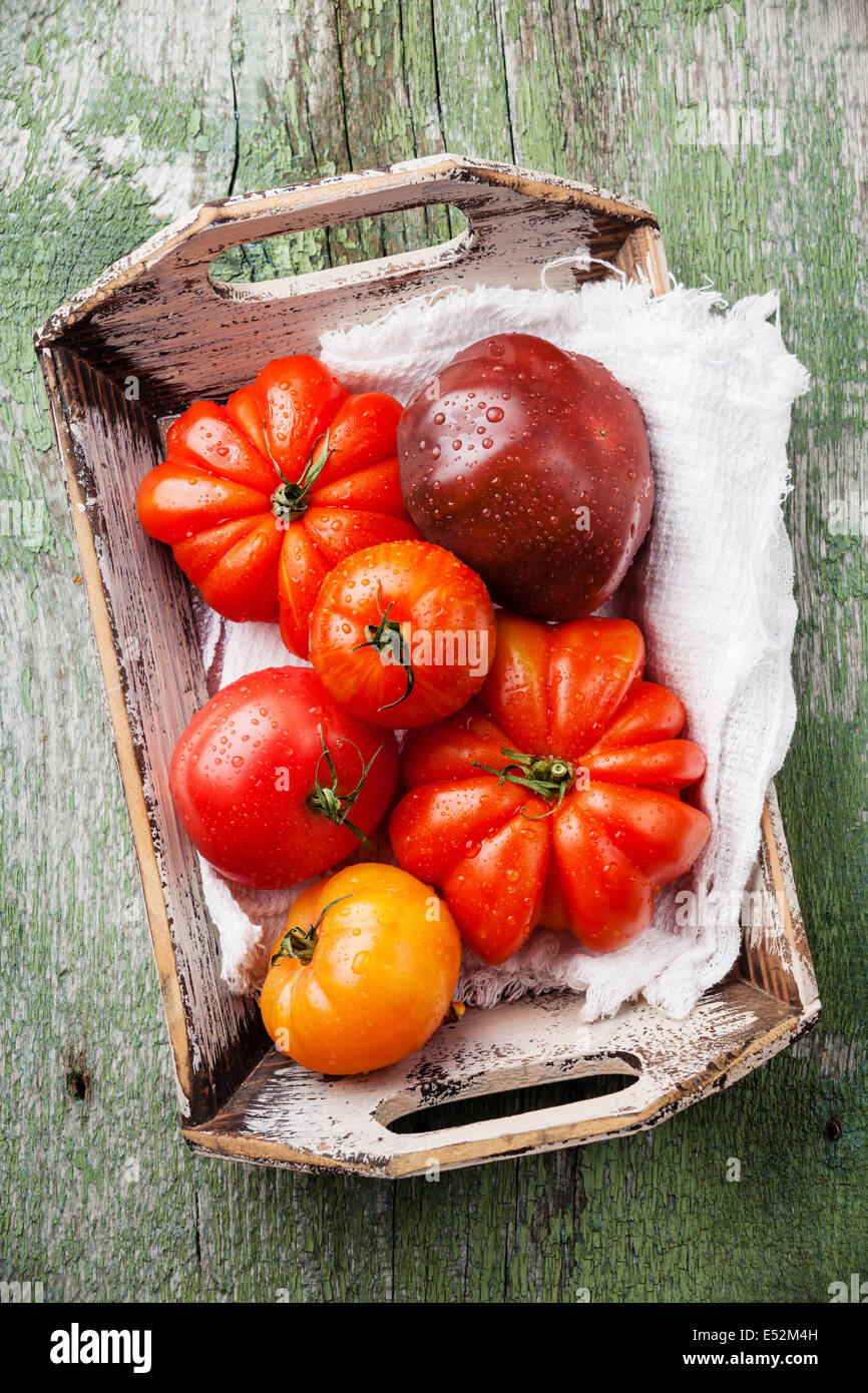 Ripe fresh colorful tomatoes in wooden box on green wooden background - Stock Image