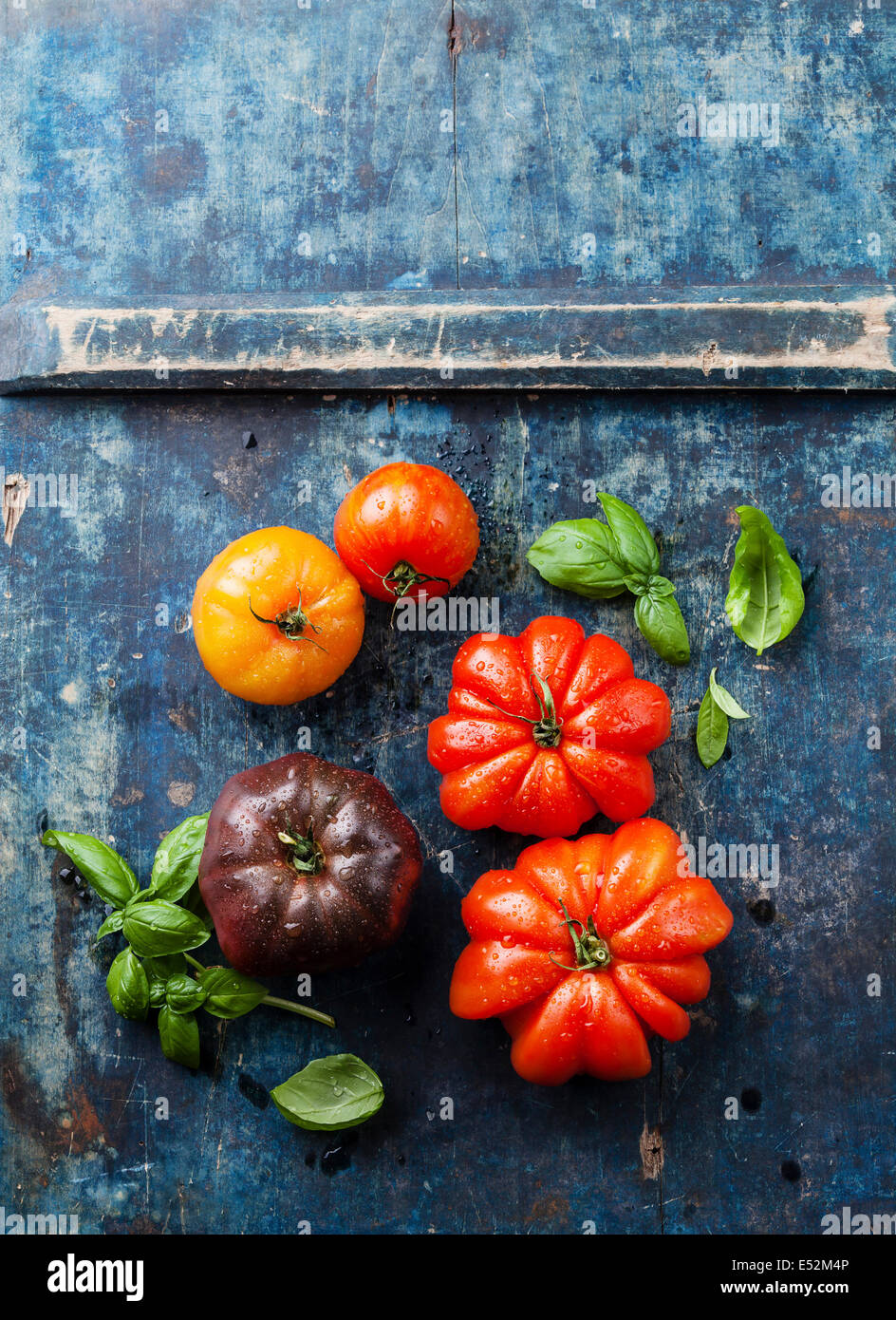 Ripe fresh colorful tomatoes on blue wooden background - Stock Image