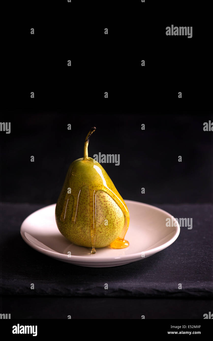 Green pear coated in honey sitting on a white plate. Slate, black, moody setting. - Stock Image