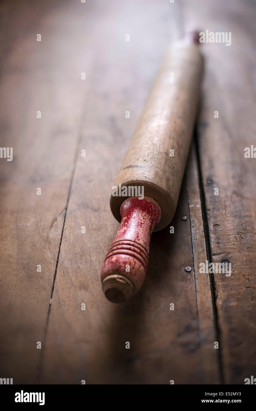Antique, rustic rolling pin with red handles on rustic wood surface. - Stock Image