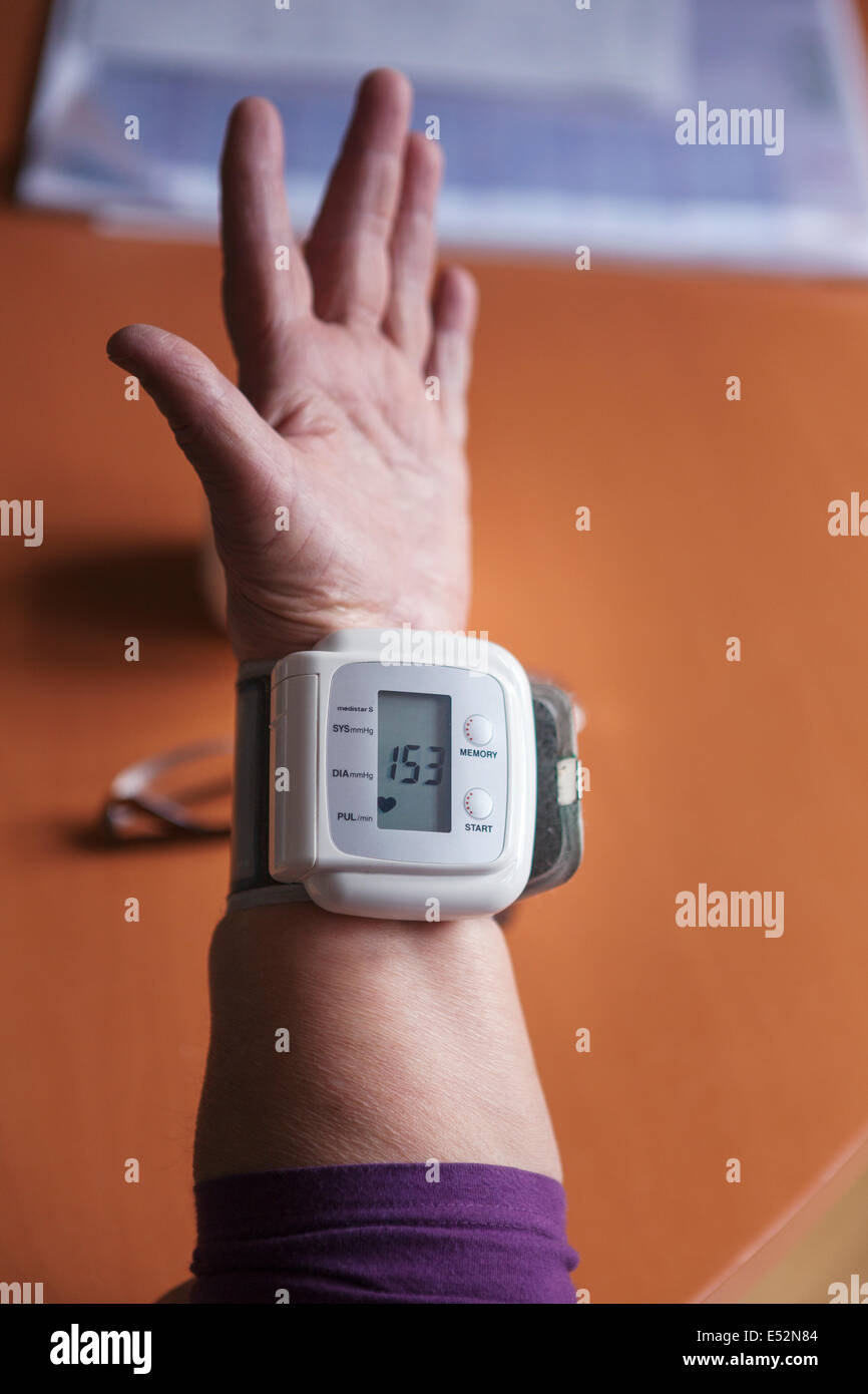Elderly woman checking her blood pressure at home - Stock Image