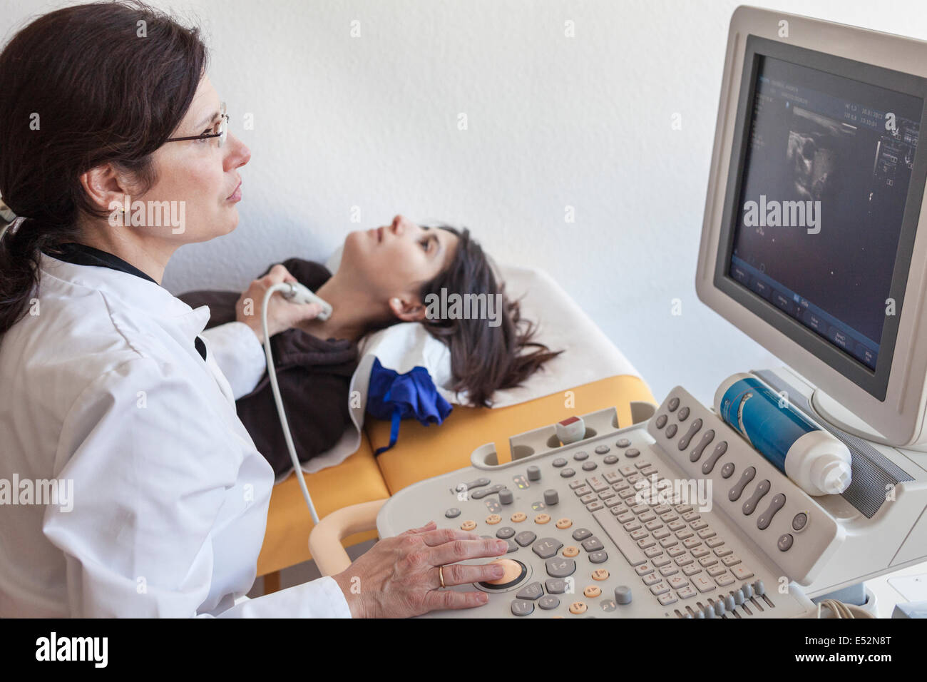 Doctor performs ultrasound on the thyroid gland - Stock Image