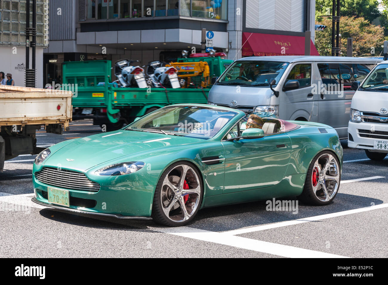 An Aston Martin stops at a traffic light in the upscale district of Ginza in Tokyo, Japan. - Stock Image