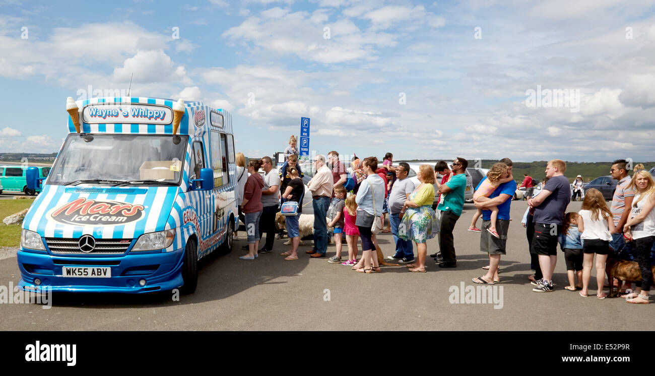 Queue of patient holiday makers waiting for ice cream from a van parked in a Welsh seaside car park in summer - Stock Image