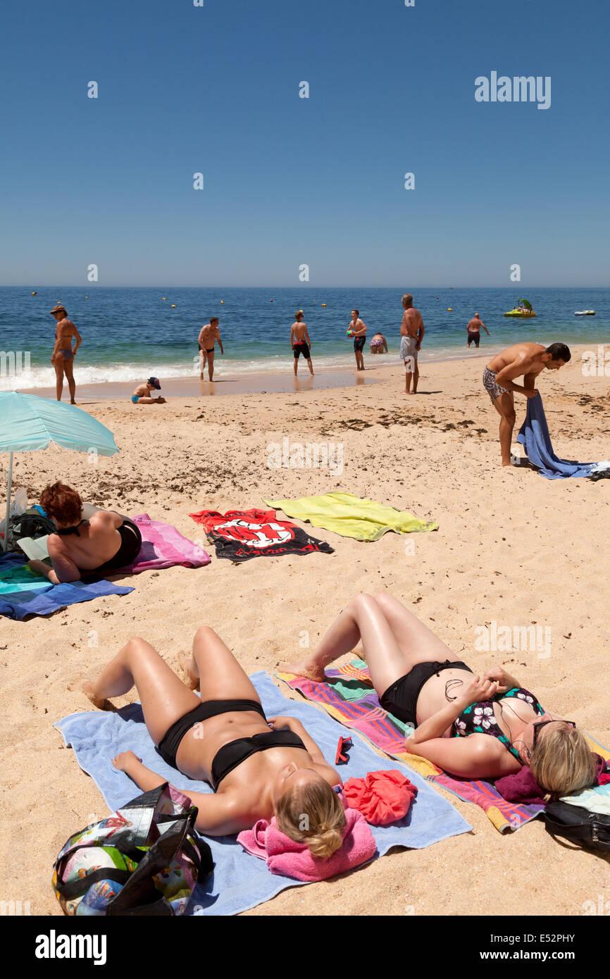 Sunbathers sunbathing on a beach summer holiday, Vale Centeanes beach, the Algarve Portugal Europe - Stock Image