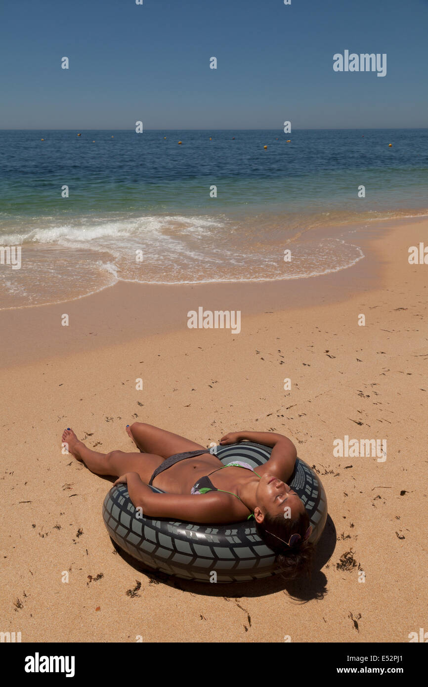Young woman sunbathing and getting a suntan on the beach, Algarve Portugal Europe - Stock Image