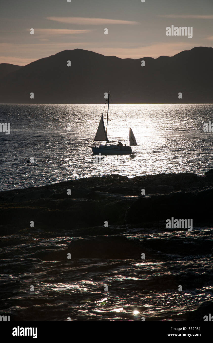 Boat in silhouette at sunrise off the coast of Anglesey Wales UK Stock Photo