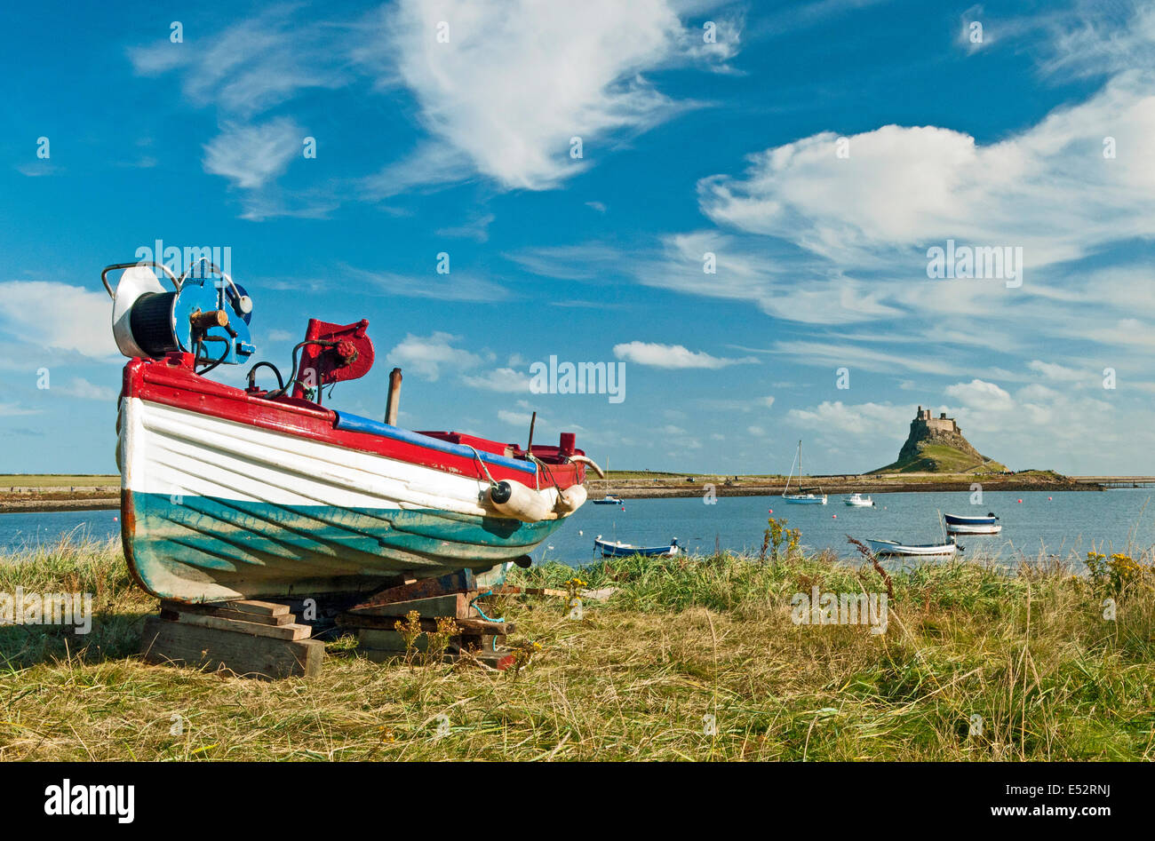 Lindisfarne Castle and Fishing Boat on Holy Island Northumberland on a sunny summer day - Stock Image