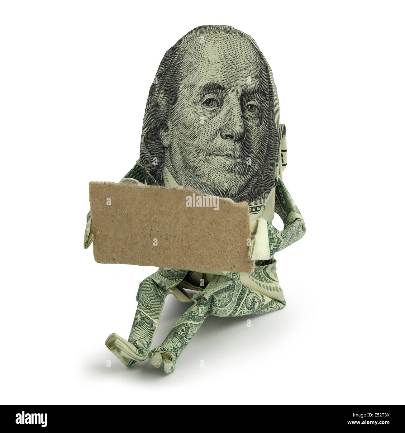 Origami human figure made of U.S. paper currency sitting with a blank cardboard sign held in front of him as if - Stock Image