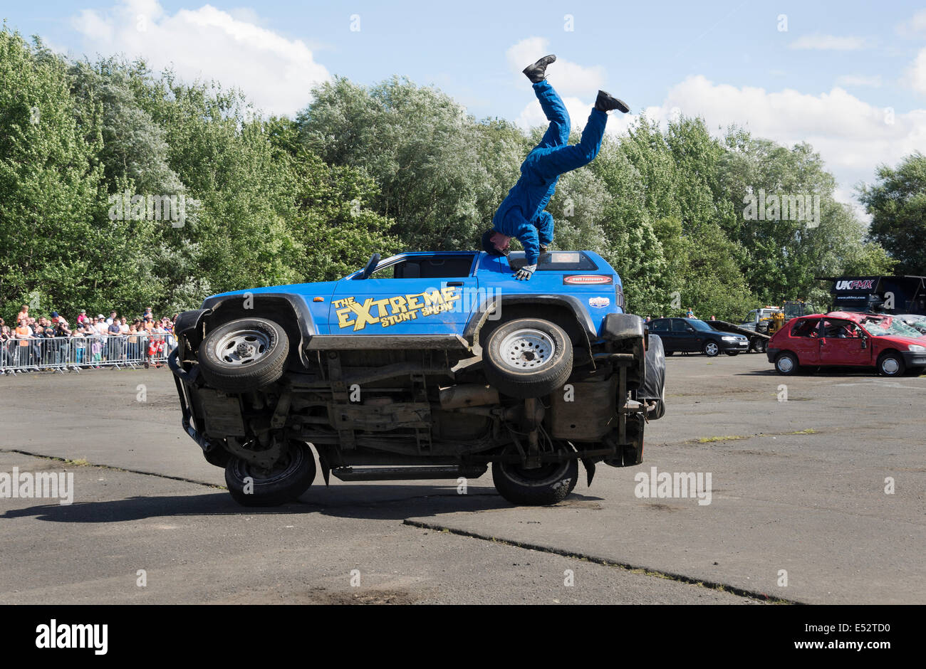 Stunt driving on two wheels with passenger doing headstand. - Stock Image