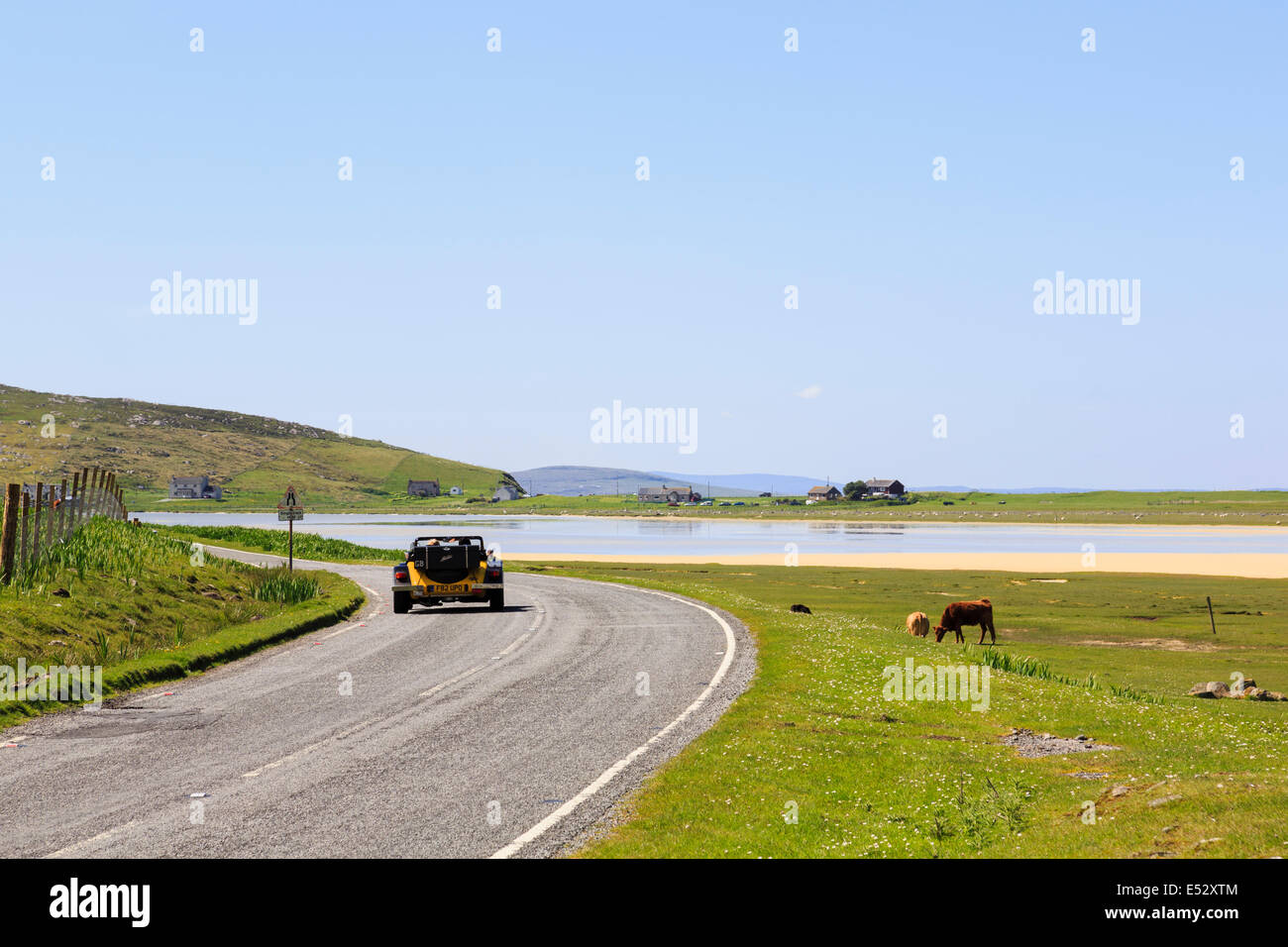 Open top sports car driving on an unfenced country coast road by Traigh Scarasta beach Isle of Harris Outer Hebrides - Stock Image