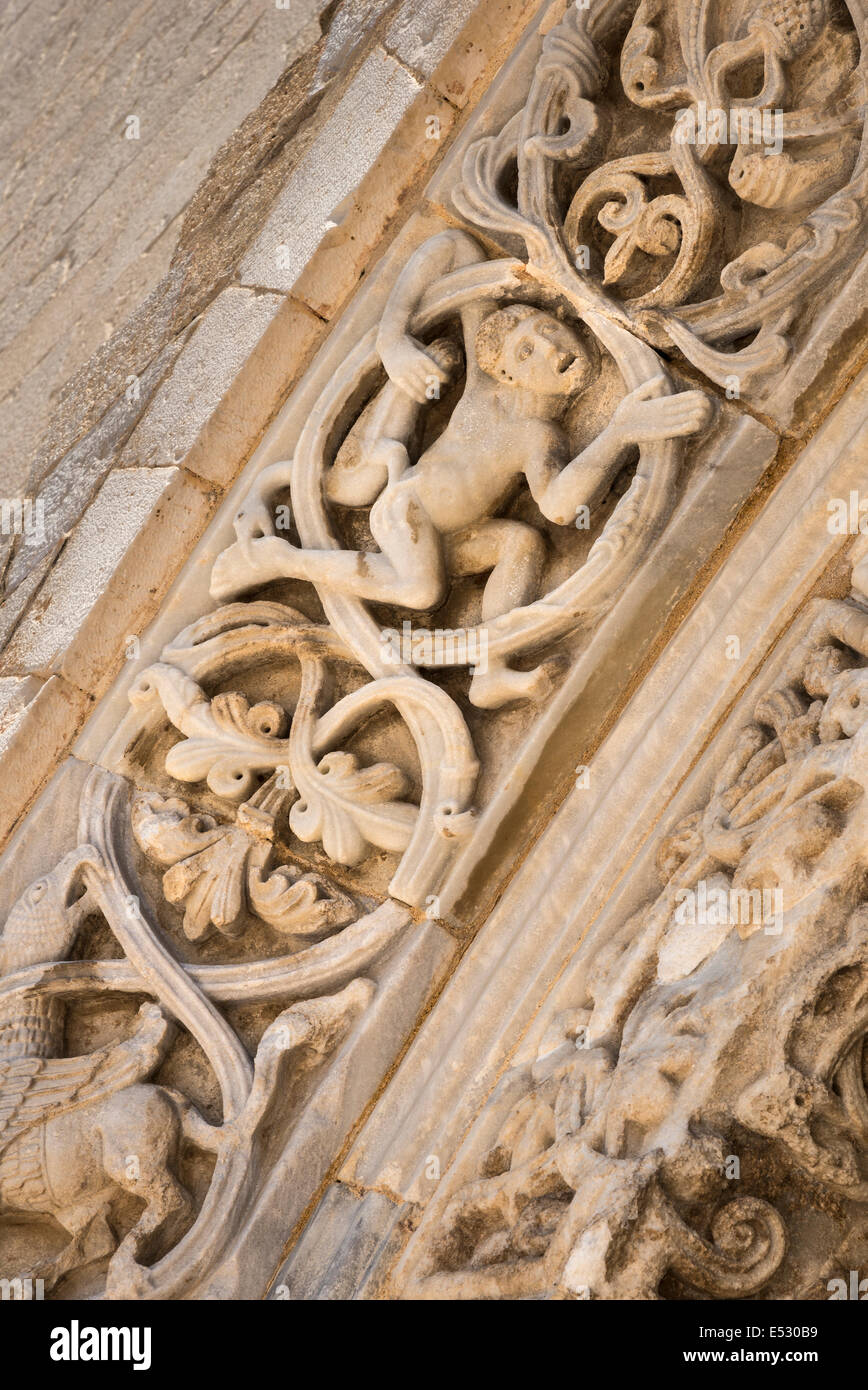 Detail of a man holding a goose on the carved romanesque surround  to the doors of the 12th century romanesque Cathedral - Stock Image