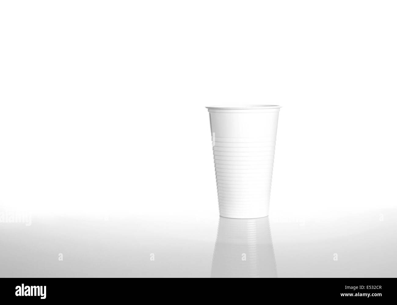 White plastic drinking cup isolated over white - Stock Image