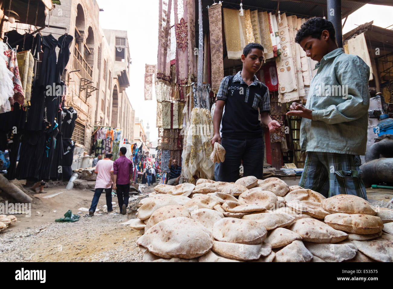 Bazaar street scene with child selling bread. Islamic Cairo, Egypt - Stock Image