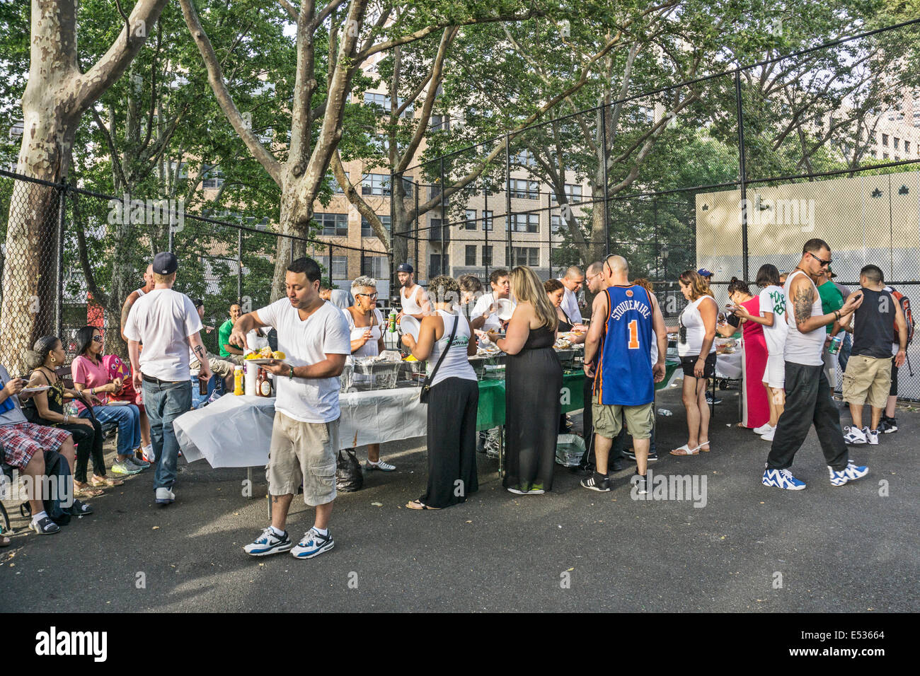 hungry people in serving line for delicious picnic supper as man leaves table with plate piled high with corn & - Stock Image