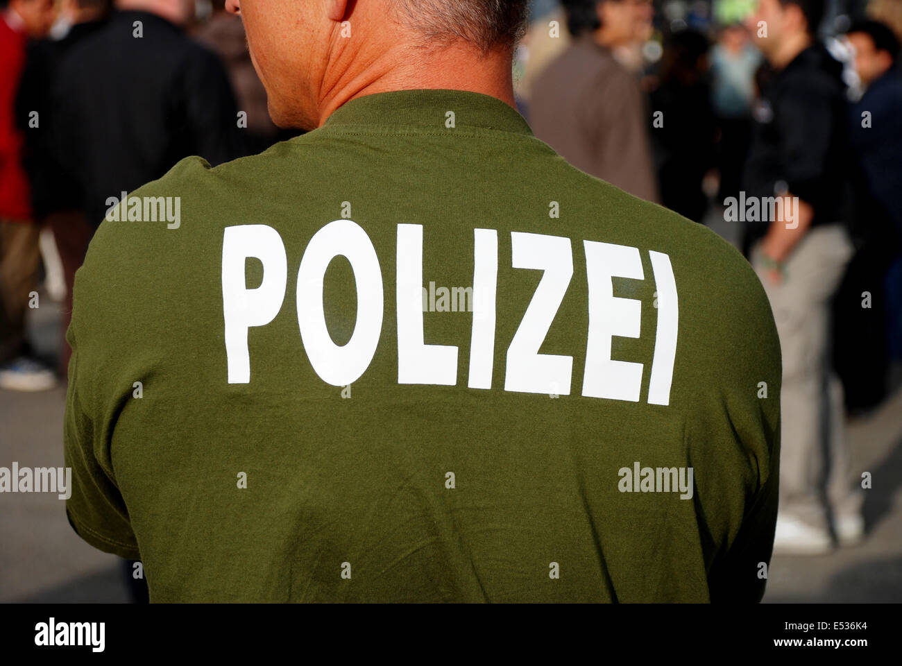 A German cops stands watching a crowd of German Iranians protesting in Kassel, Deutchland during the green revolution. Stock Photo