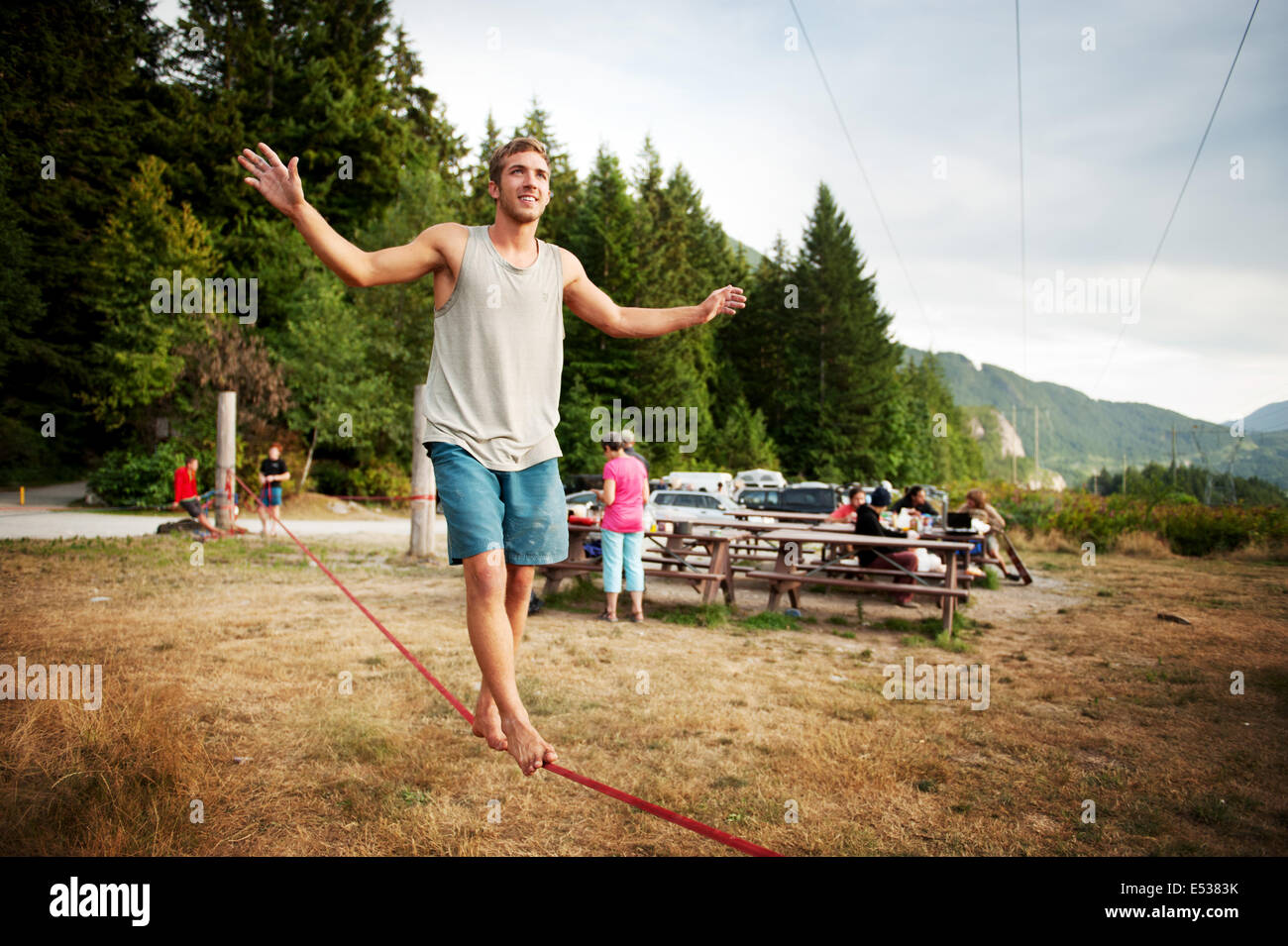 A man walks a slack line at sunset.  Life along the Stawamus Chief Provincial Park campsite, also known as the Squamish - Stock Image