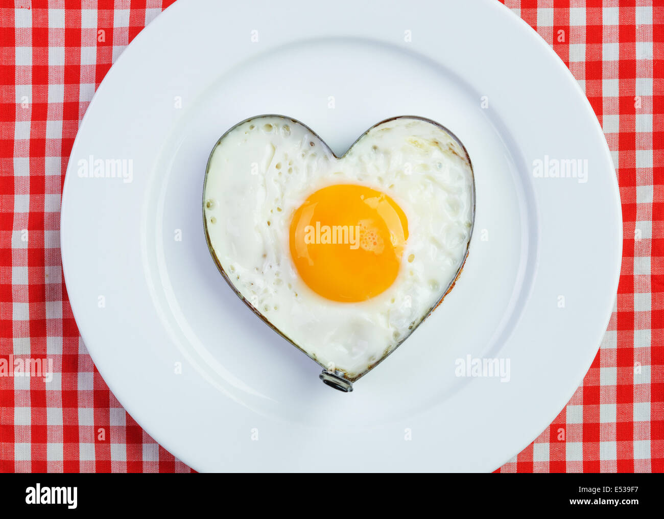 Fried egg  in heart shape on vintage tablecloth. Breakfast for a loved one - Stock Image