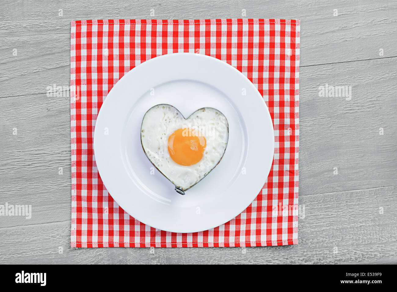 Fried egg  in heart shape on vintage table. Breakfast for a loved one - Stock Image