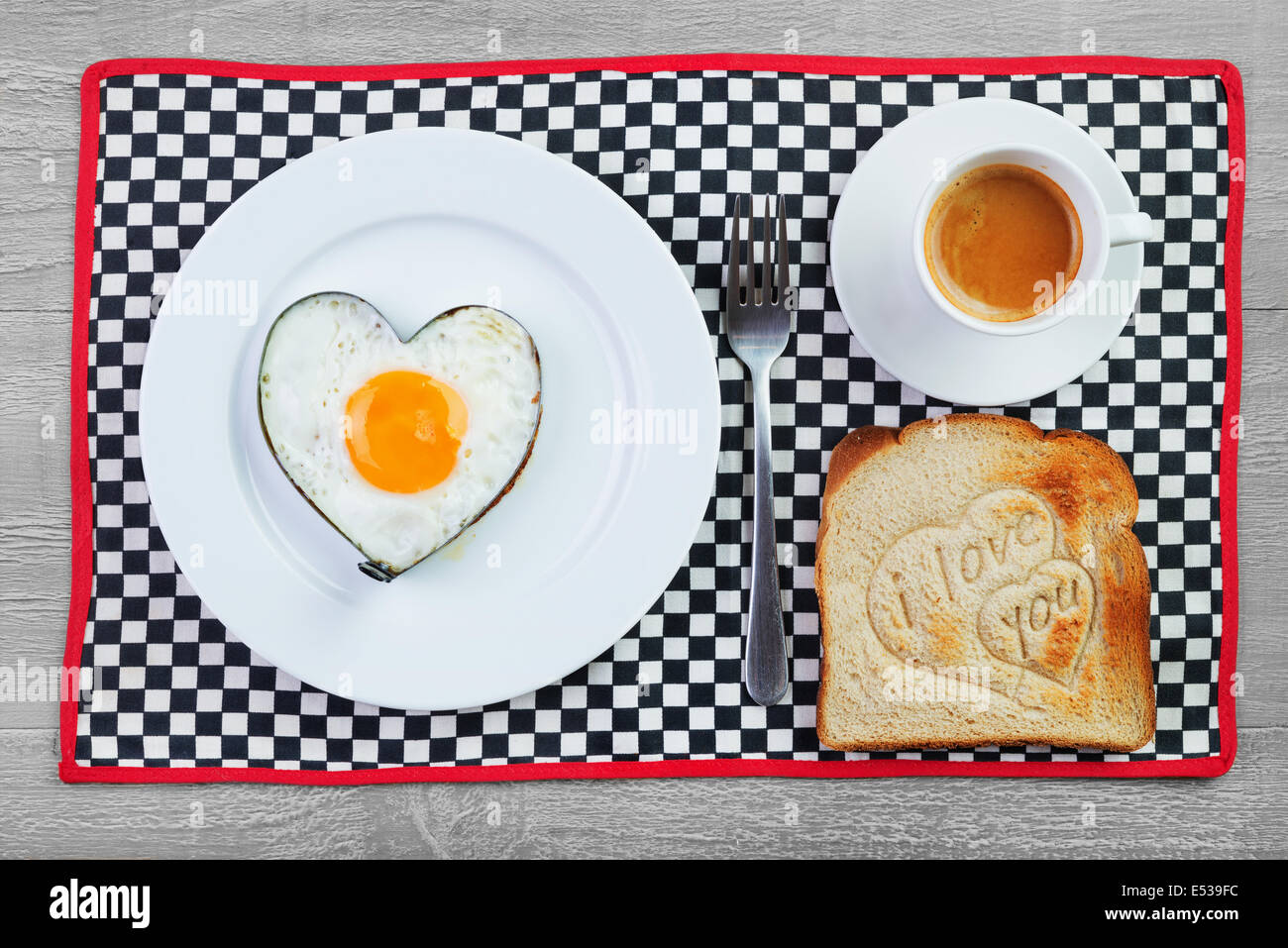 Fried egg  in heart shape  and toast with love message.Breakfast for a loved one - Stock Image