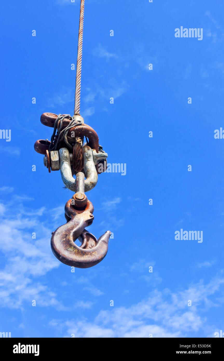 industrial crane hook against blue sky - Stock Image