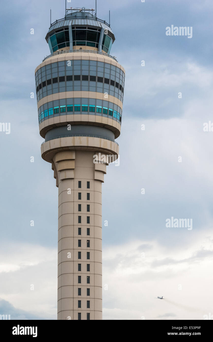 The air traffic control tower stands sentinel over Atlanta International Airport as a passenger jet climbs into - Stock Image