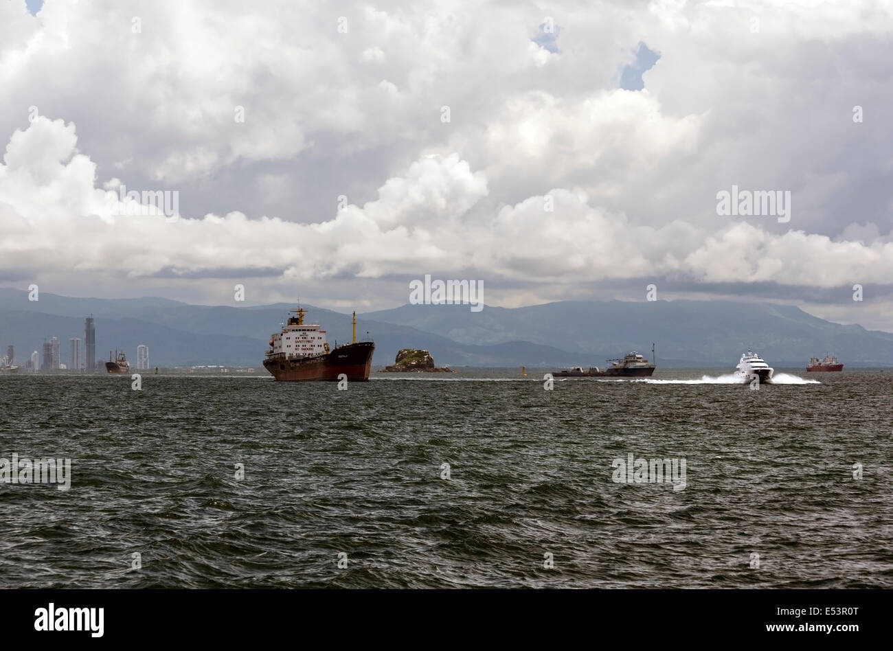 Yacht going to Taboga island and cargo ships waiting to cross Panama Canal in the Gulf of Panama with the Panama - Stock Image