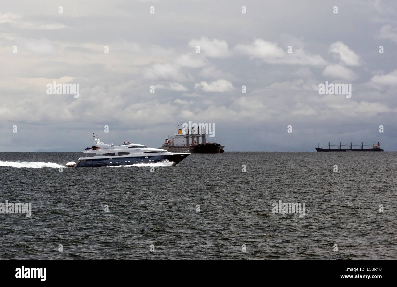 Yacht going to Taboga island and cargo ships waiting to cross Panama Canal in the Gulf of Panama - Stock Image
