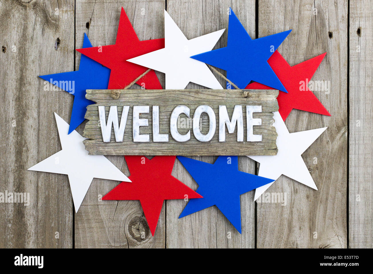 Welcome Sign With Red White And Blue Stars Hanging On Rustic Wooden