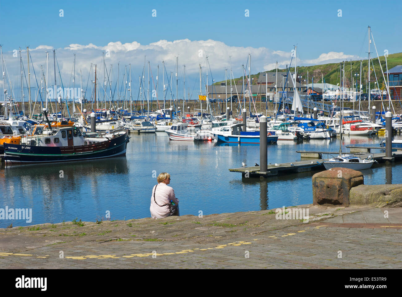Woman sitting next to the marina, Whitehaven, West Cumbria, England UK - Stock Image