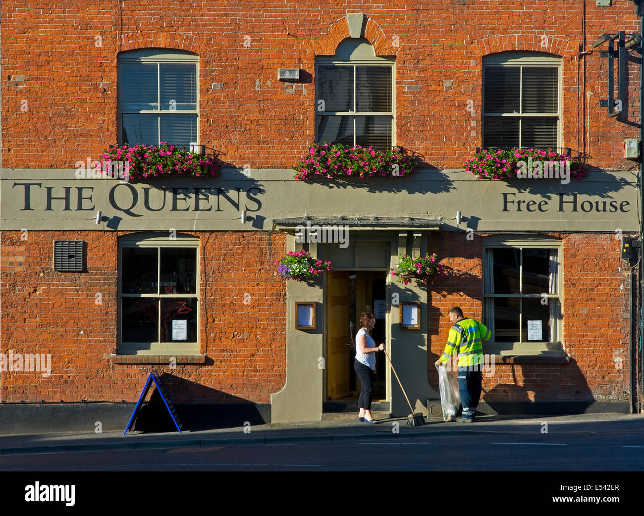 Sweeping up rubbish outside the Queens, Ludlow, Shropshire, England UK - Stock Image