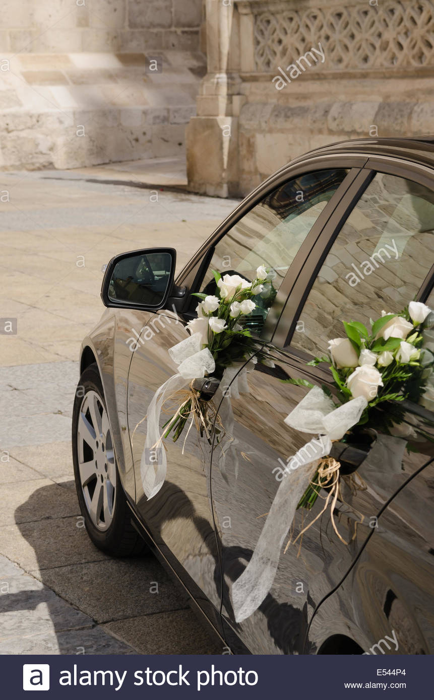 Wedding Car In Black Decorated With White Flowers Stock Photo