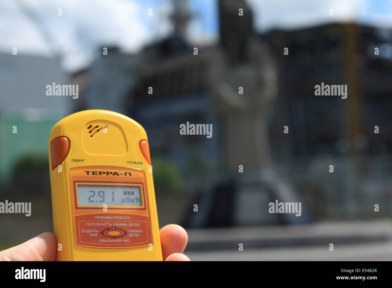 Tourist with a dosimeter takes a radiation reading with the abandoned Chernobyl reactor 4 in the background. - Stock Image