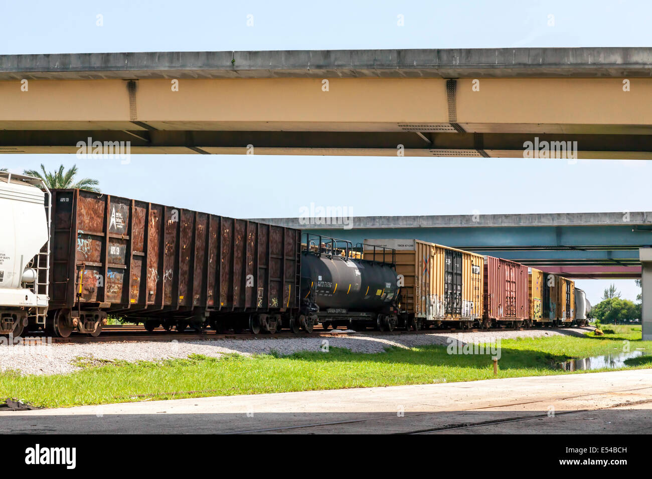Rusting RR freight cars and tanker car sitting on a railroad siding under box beam highway overpasses. - Stock Image