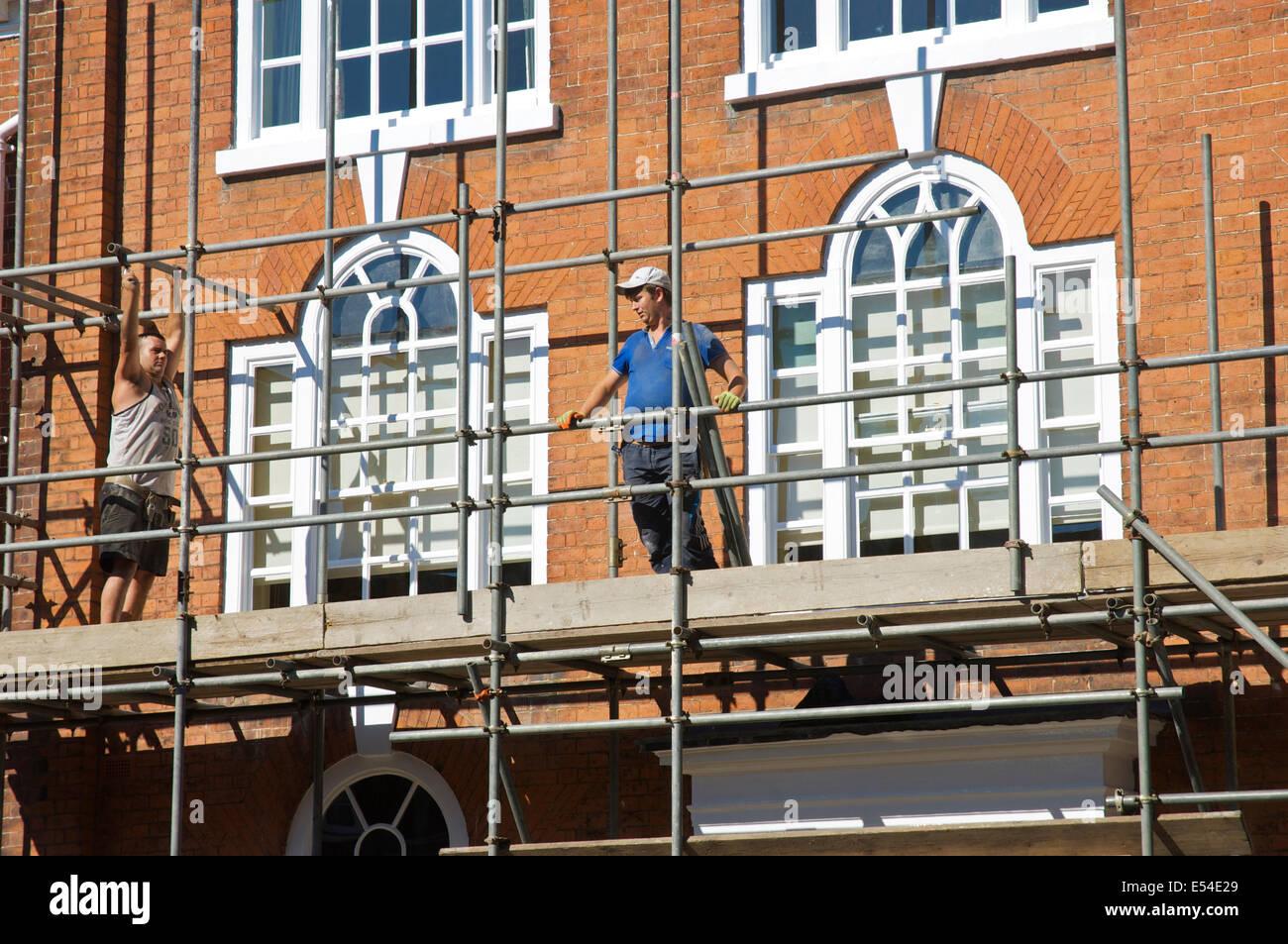 Two men dismantling scaffolding on Georgian building, Ludlow, Shropshire, England UK - Stock Image