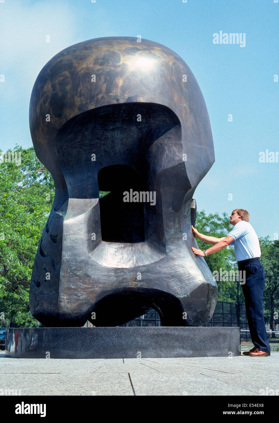 """A man gets a close look at """"Nuclear Energy,"""" an abstract bronze sculpture by Henry Moore on the University of Chicago Stock Photo"""