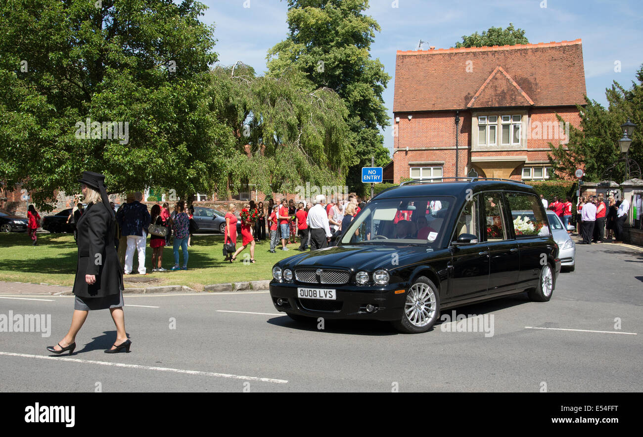 Jaguar hearse carrying a red and white coloured coffin in a funeral parade Marlow Buckinghamshire UK - Stock Image