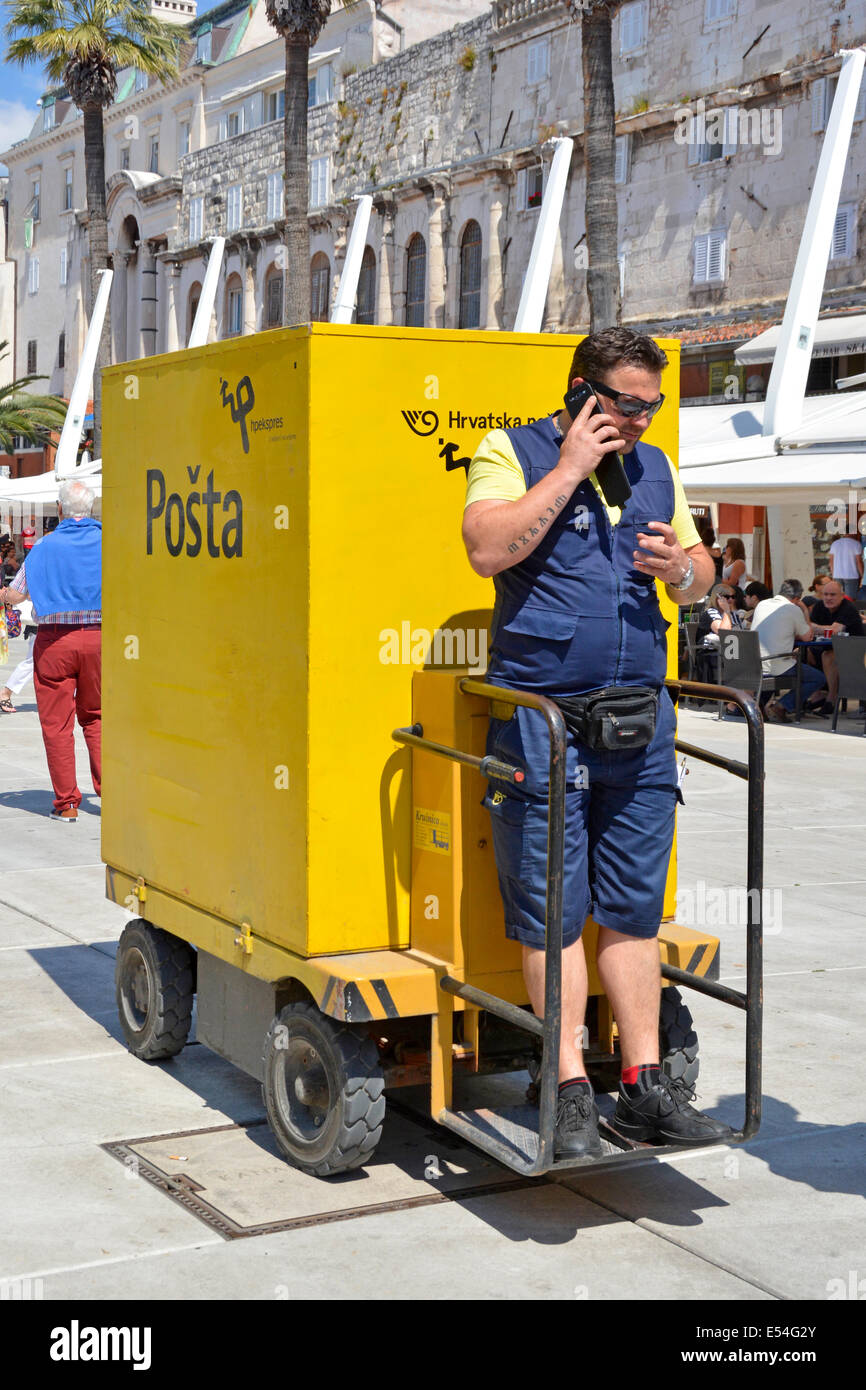 Postman making a phone call whilst stationary on an unusual Posta delivery vehicle in Split town centre postal service - Stock Image