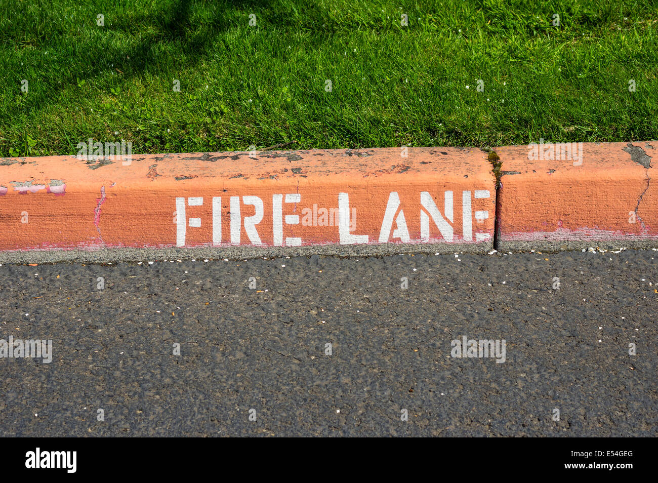 A red painted curb with a fire lane warning sign - Stock Image