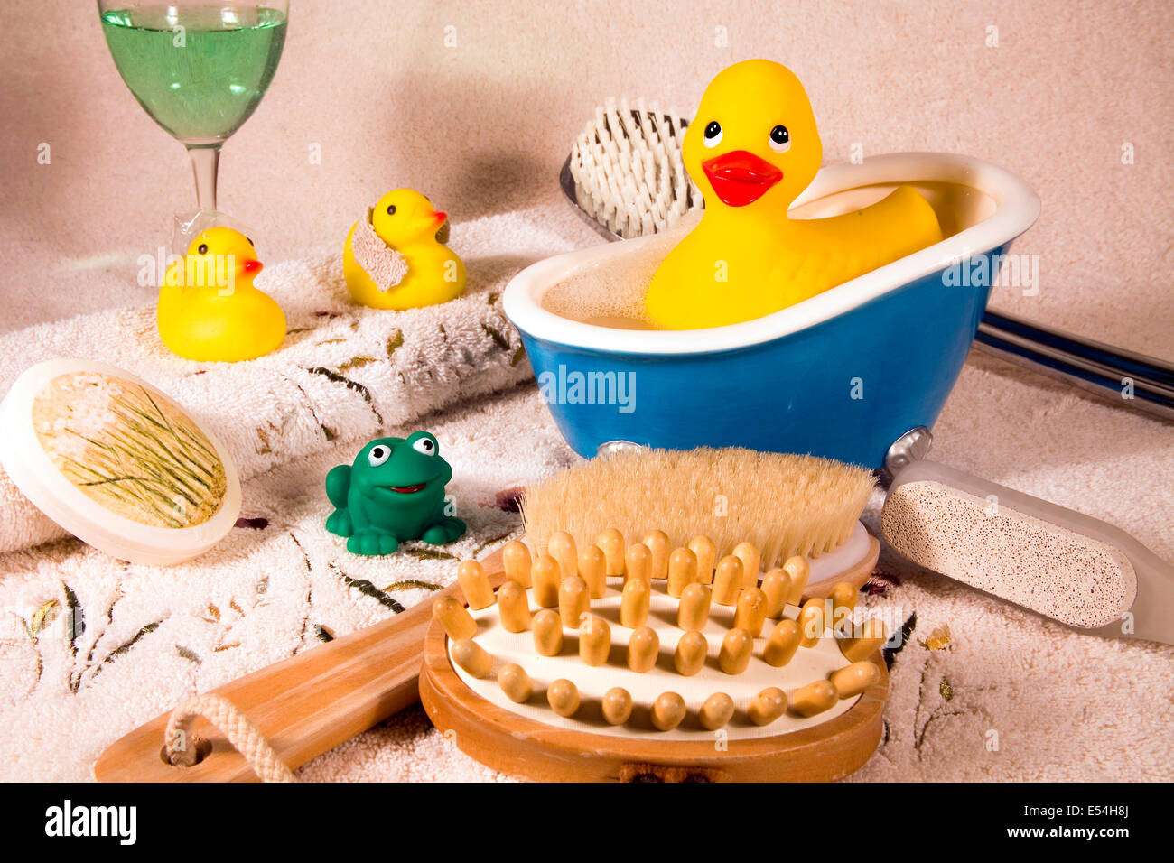 Spa setting with rubber duckies in bath tub, in shower cap, with ...